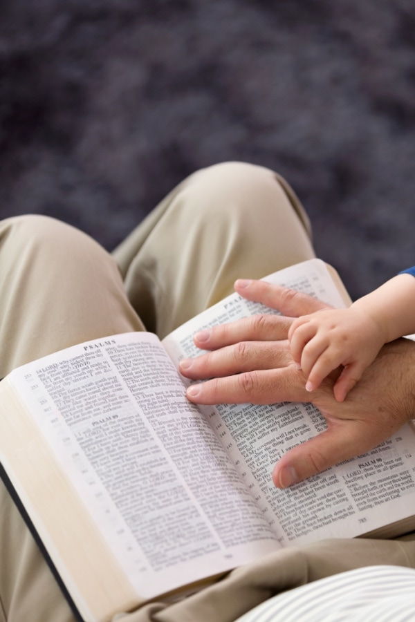 man putting his hand on an open Bible