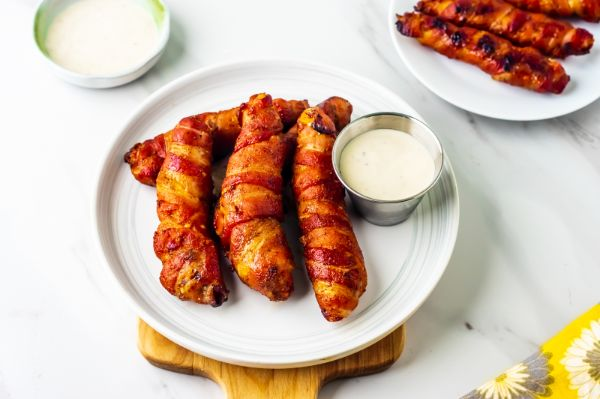 plate holding chicken tenders wrapped in bacon after being cooked in air fryer