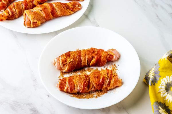 rolling bacon wrapped chicken in spices