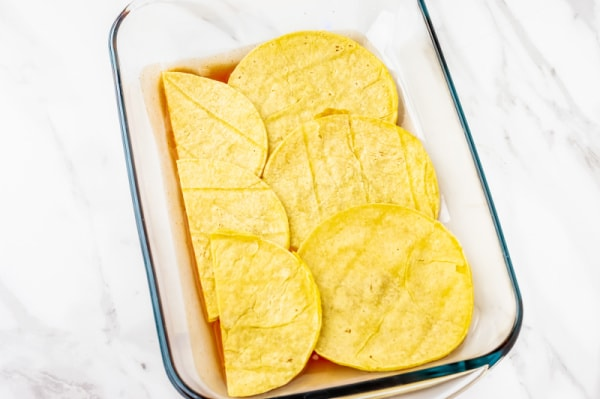 corn tortillas layered in a baking pan