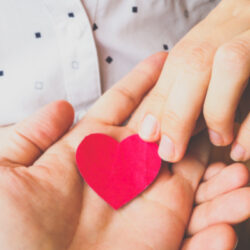 families hands holding small red heart