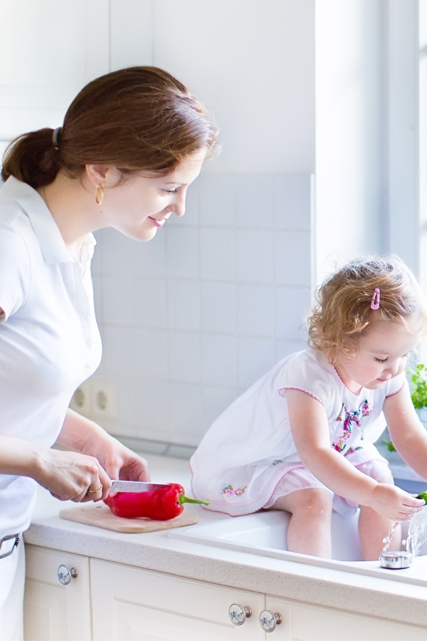 mom standing at sink withy young child sitting with feet in sink