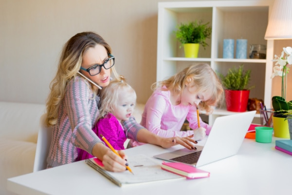 mom working at home with two small children
