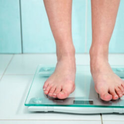 feet standing on bathroom scale