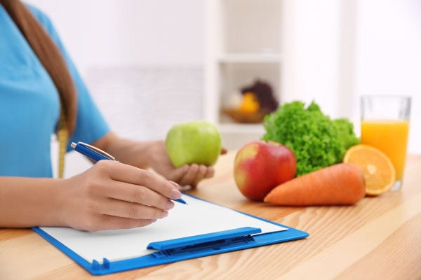 fruits and veggies on counter with woman writing on white paper