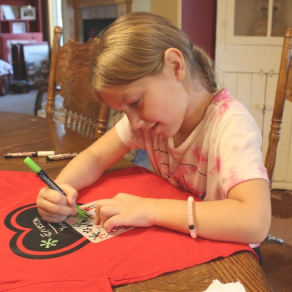 small child coloring on a t-shirt