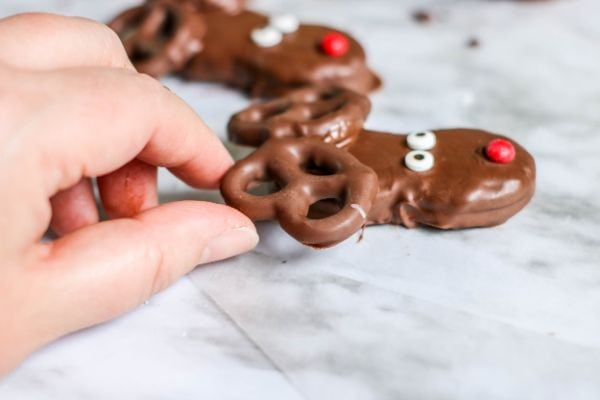 making a reindeer face with Nutter Butters and pretzels