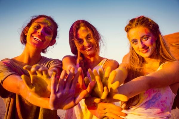 three girls with paint on their hands smiling