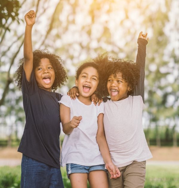 three children smiling in the sun