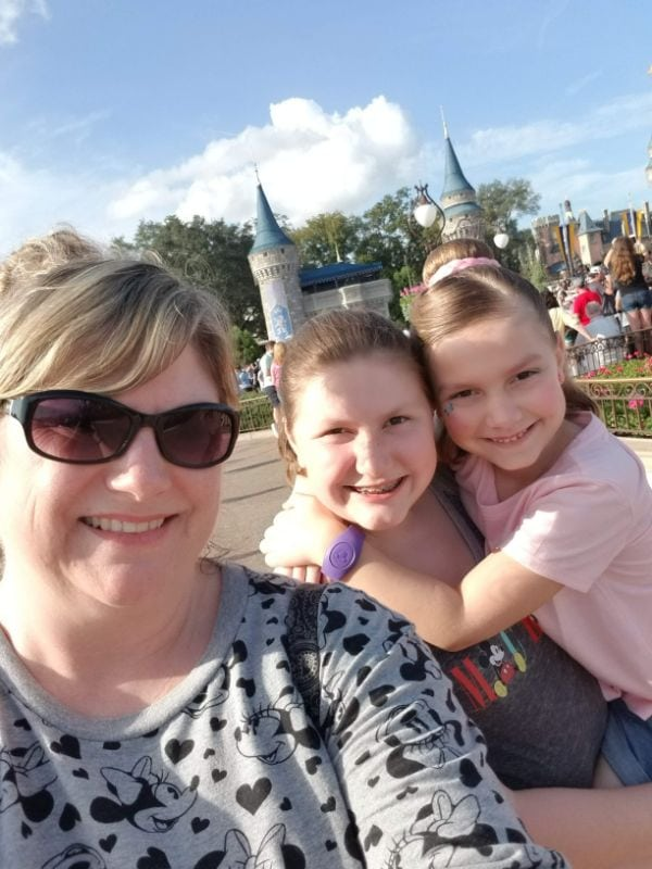 three people at Disney world in front of castle