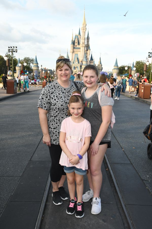 mom and two girls in front of Cinderella's castle at Disney World