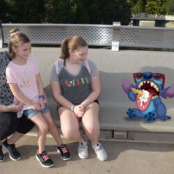 three people sitting down looking at a cartoon character
