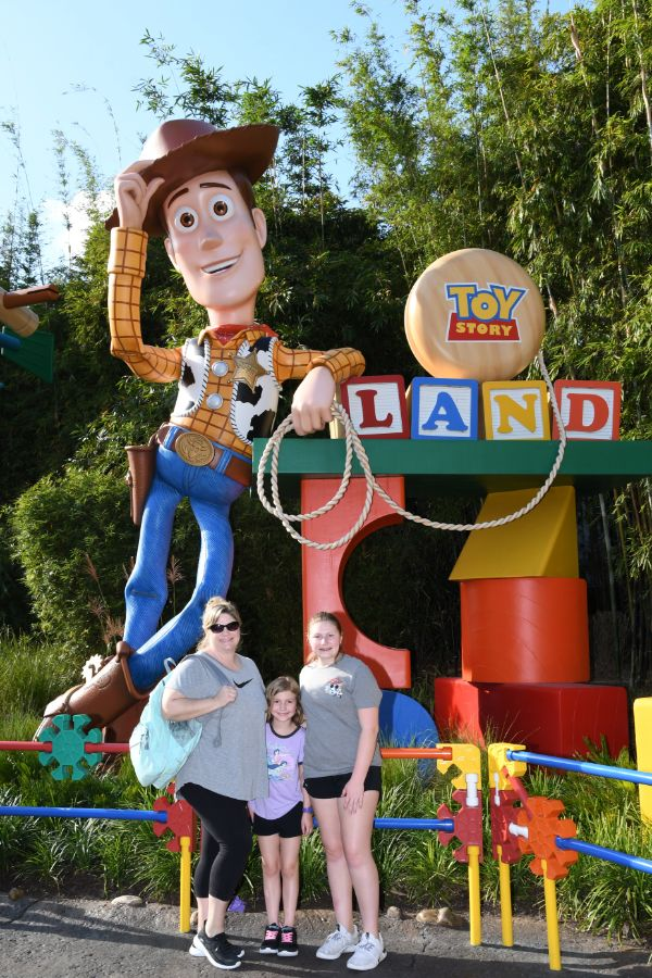 three people posing in front of Toyland at Hollywood Studios