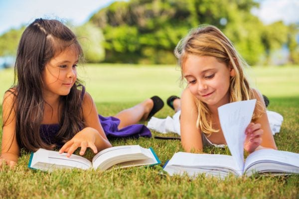 two girls reading in the grass