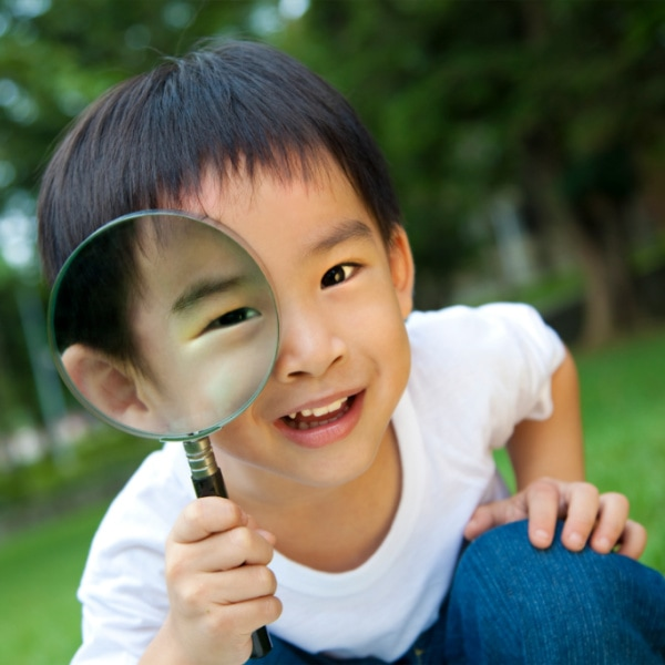 little boy looking in a magnifying glass