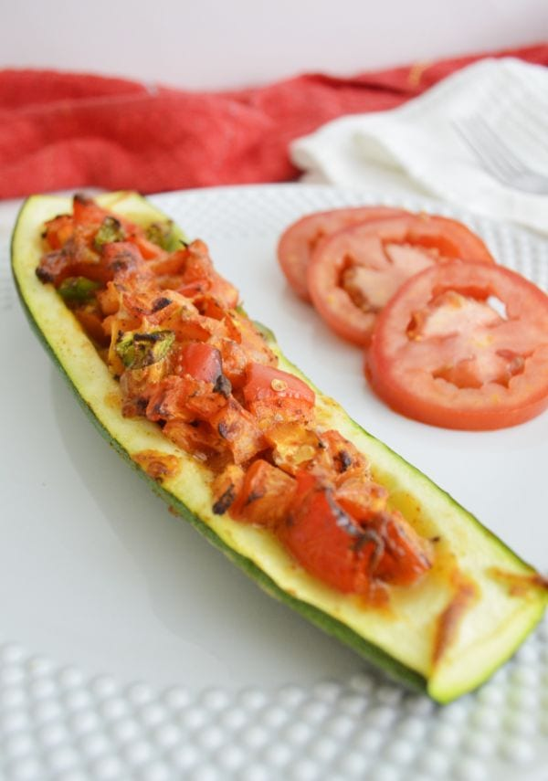 veggie stuffed zucchini boats on a plate with sliced tomatoes