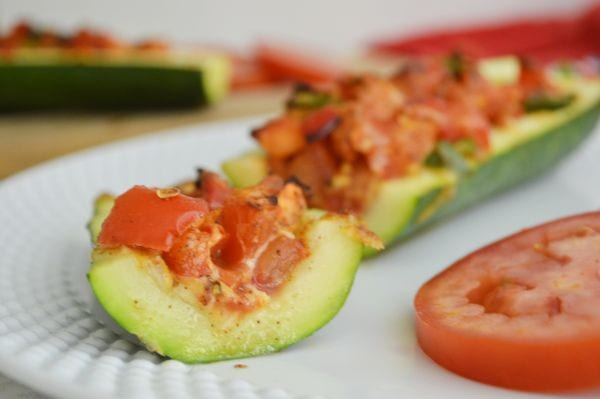 close up photo of cooked zucchini boats on a white plate
