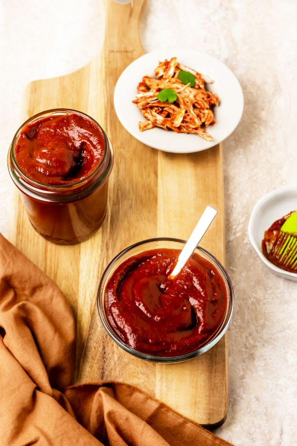 jar of homemade sugar-free BBQ sauce on a wooden board with a bowl of sauce