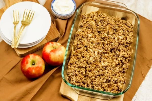 pan of baked WW apple crisp sitting on table with an apple