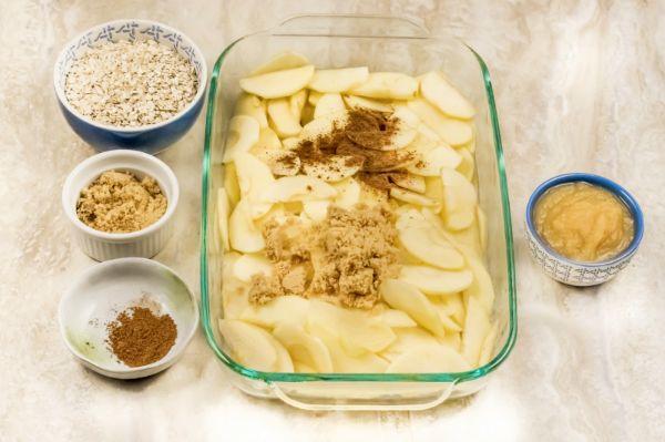 layering apple crisp ingredients in a baking dish