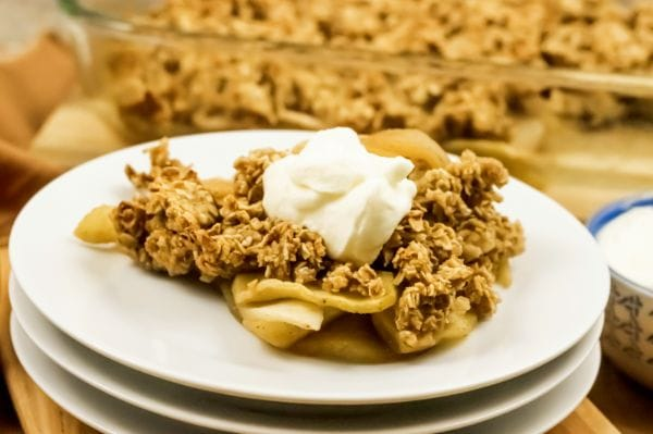 piece of apple crisp on a white plate with whipped topping