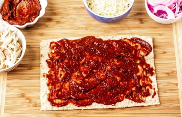 adding bbq sauce to a slice of chicken pizza