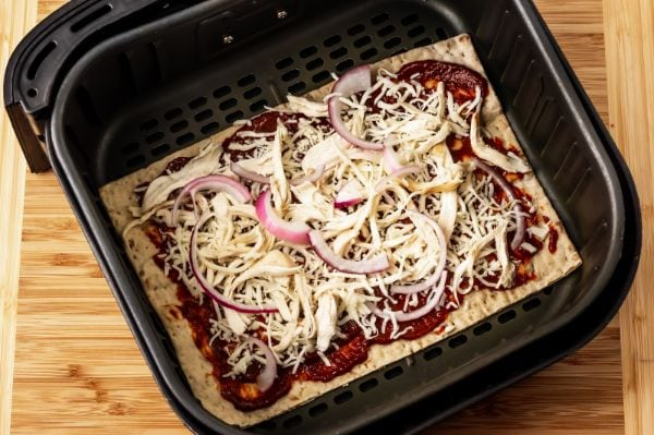 uncooked bbq chicken pizza in the air fryer basket ready to cook