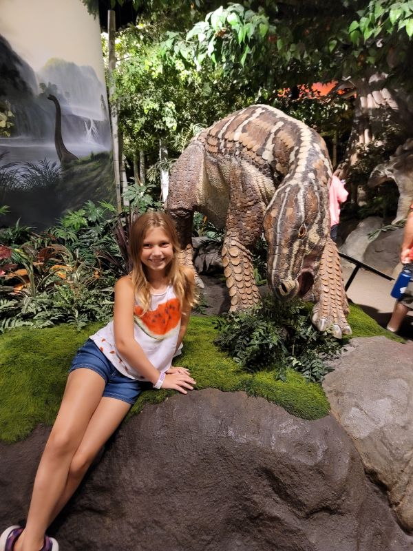 young girl standing in front of a small dinosaur at the Creation Museum