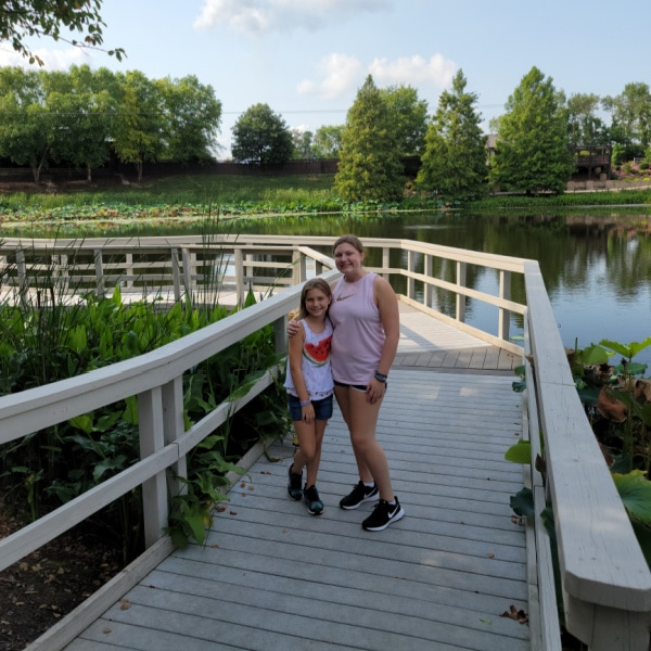 2 girls standing on a bridge in the botanical gardens at the Creation Museum