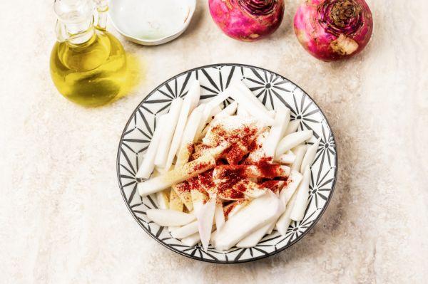sliced turnips in bowl with seasoning