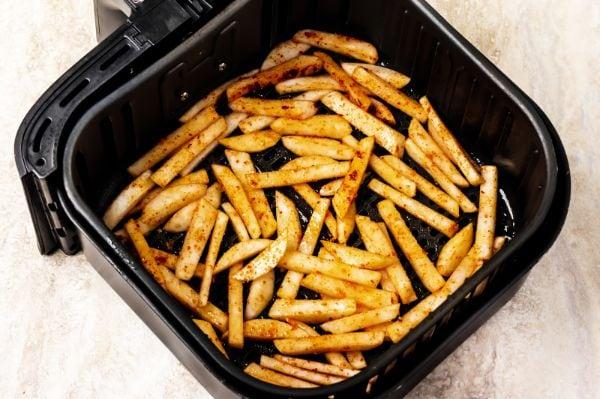 sliced turnip fries in air fryer basket ready to cook